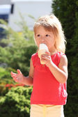 Little girl eating ice cream outdoors — Stock Photo