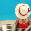 Little girl in a hat floating in the pool — Stock Photo