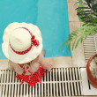 Stock Photo: Little girl in a hat floating in the pool