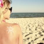 Of sun cream on the female back on the beach — Stock Photo #39694573