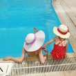 Stock Photo: Little girl in a hat with mother in swimming pool