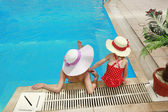 Little girl in a hat with mother in swimming pool — Stock Photo