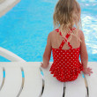 Stock Photo: Girl sitting near pool
