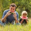 Stock Photo: Father with a small daughter eat watermelon on the grass