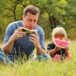Father with a small daughter eat watermelon on the grass — Stock Photo #41453911