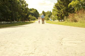 Grandfather with granddaughter walk along the road — Stock Photo