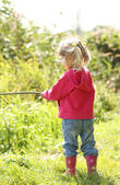 Beautiful little girl in nature playing with a stick  — Stock Photo