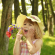 Stock Photo: Beautiful little girl on nature with bouquet of flowers