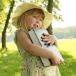 Stock Photo: Beautiful little girl with Bible in nature