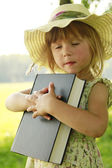 Beautiful little girl with the Bible in nature  — Stock Photo
