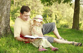 Young father with his little daughter reads the Bible — Foto de Stock