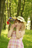 Beautiful little girl on nature with a bouquet of flowers — Stock Photo