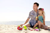 Dad and little daughter playing on the beach — Stockfoto
