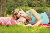 Mama and her little daughter lie on the grass — Stock Photo