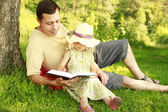 Father with  daughter reads the Bible — Stock Photo