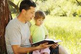 Jonge vader met dochter leest de bijbel — Stockfoto