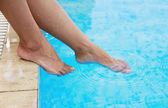 Female legs in the water pool — Stock Photo