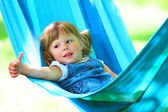 Beautiful little girl lying in a hammock — 图库照片