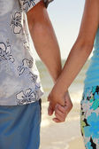 Couple holding hands on the sea shore — Stock Photo