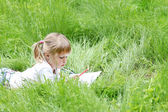 Beautiful little girl draws on nature — Photo
