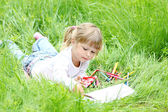 Beautiful little girl draws on nature — Stock Photo