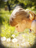 Little girl with dandelion in nature — Stock Photo