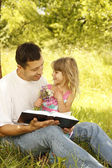 Father with little daughter reads the Bible — Stock Photo