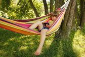 Girl with smartphone in hammock — Stock Photo