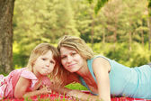 Mother and daughter lie on the grass — Stock Photo