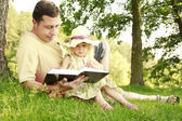 Father little daughter reads the book — Stock Photo
