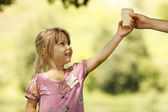 Girl takes ice cream from hand — Stock Photo