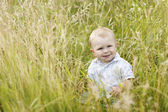 Little boy playing in tall grass — Stock Photo