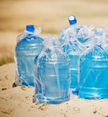 Many bottles of water standing in the sand — Stock Photo
