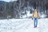 Man walks along a snowy road — Stock Photo