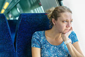 Sad woman at the window of a train — Stock Photo