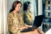 The young woman at the window with a laptop — Stock Photo