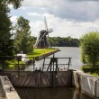 Lock gates and Dutch windmill - Stock Photo