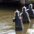Bollards in a canal of a Dutch city - Stock Photo