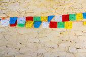 Buddhist tibetan prayer flags against wall — Stock Photo