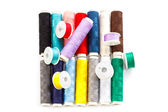 Several multicolored bobbins and coils with sewing thread — Stock Photo