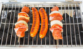 Sausages and meat skewers on the barbecue — Stock Photo
