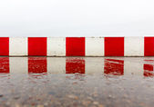 Red white concrete wall on the asphalt — Foto Stock