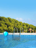 Swimming pool in mediterranean landscape — Stock Photo