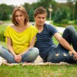 Young pretty pregnant woman with young man outdoor in the park — Stock Photo
