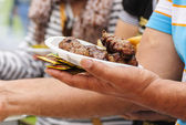 Man holding in one hand a plate full of mici and some mustard — Stock Photo