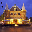 De Waag building in Amsterdam the Netherlands by night - Stock Photo