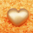 Heart from gold in orange confetti — Stock Photo