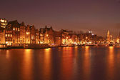 Natt i amsterdam på floden amstel med munt-tornet i th — Stockfoto