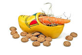 Wooden clog with straw, gingernuts and carrot — Stock Photo