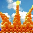 Crown from orange balloons against a blue sky - Stock Photo